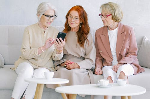 2 Women Sitting on Chair Holding Smartphone