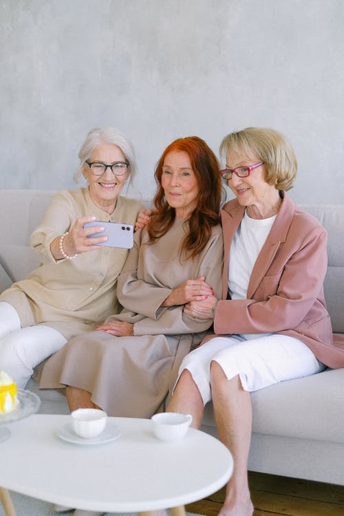 Aged women taking selfie with smartphone at table with cups