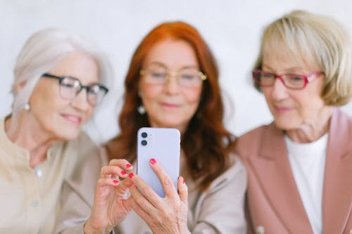 Senior women using smartphone while surfing internet