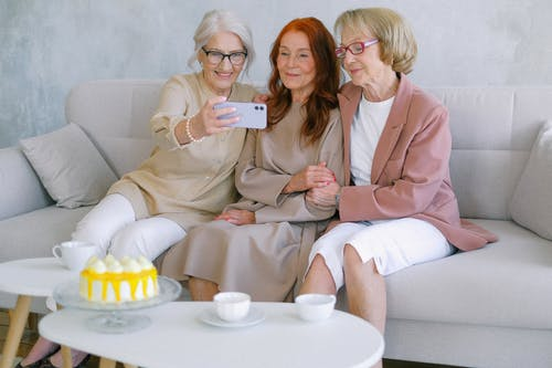 Happy senior women taking selfie on mobile phone at table with sweet delicious cake and cups
