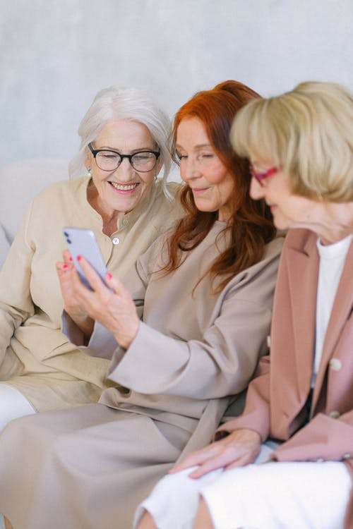 Senior cheerful women in eyeglasses looking at screen of smartphone and surfing internet together