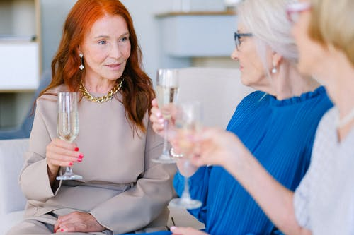 Senior women with glasses of champagne talking