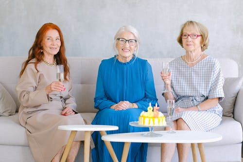 Aged cheerful women smiling and celebrating birthday while looking at camera at table with sweet cake decorated with candles