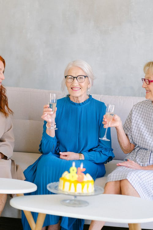 Happy aged women with glasses of champagne smiling