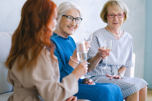 Senior positive women with glasses of champagne talking and smiling