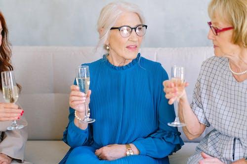 Elderly women in eyeglasses with glasses of champagne talking