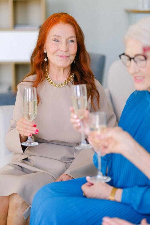 Cheerful elderly women with glasses of champagne talking and smiling