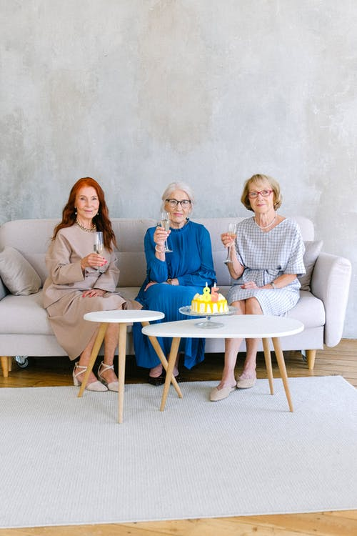 Glad elderly women with glasses of champagne at table