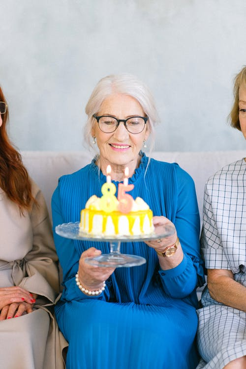 Photo Of An Elderly Woman Carrying Birthday Cake