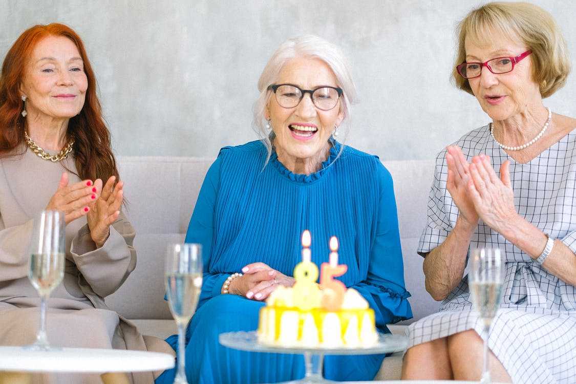 Positive elderly women in stylish clothes sitting on sofa near table with birthday cake and glasses of champagne celebrating birthday at home