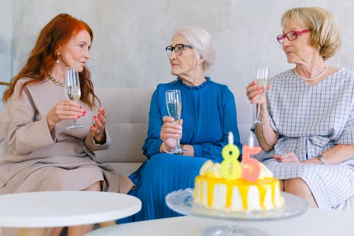Aged best friends with glasses of champagne talking at table with birthday cake decorated with candles