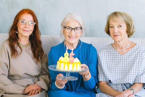 Happy elderly women with birthday cake