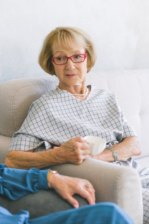 Senior female in eyeglasses and trendy dress drinking cup of coffee while speaking with crop anonymous friend