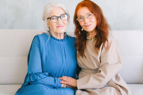 Happy aged women in eyeglasses holding hands