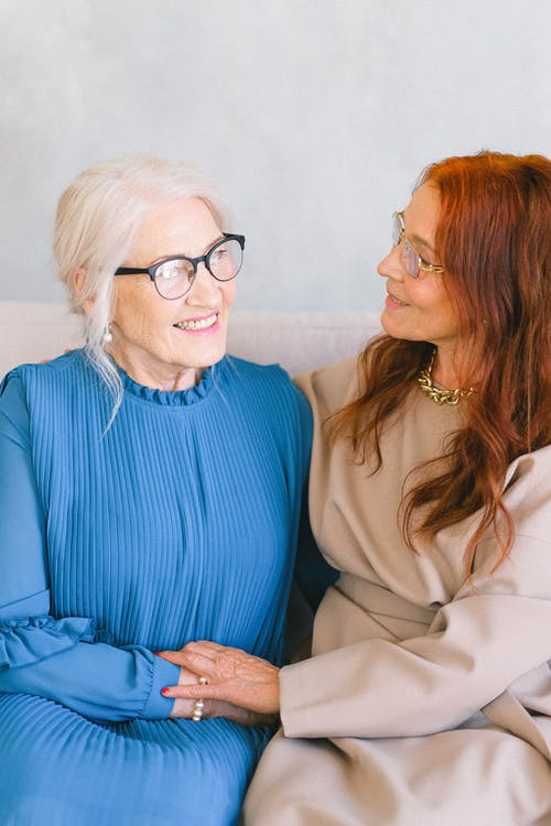 Senior cheerful women in eyeglasses and trendy dresses holding hands while smiling and talking