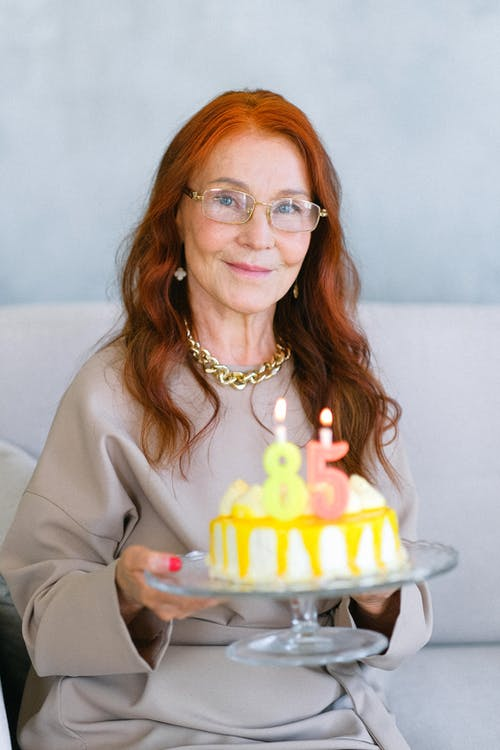 Happy aged woman with birthday cake decorated with festive candles