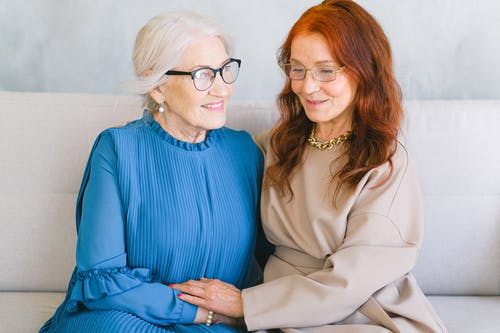 Positive elderly women in eyeglasses and elegant trendy dressing holding hands and speaking while resting on sofa