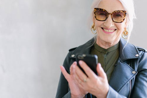Crop happy senior female in stylish jacket touching screen of mobile phone while smiling and looking at camera