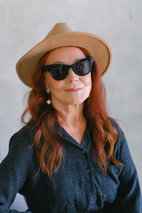 Elderly stylish female in fashionable sunglasses and hat looking at camera while smiling on gray background