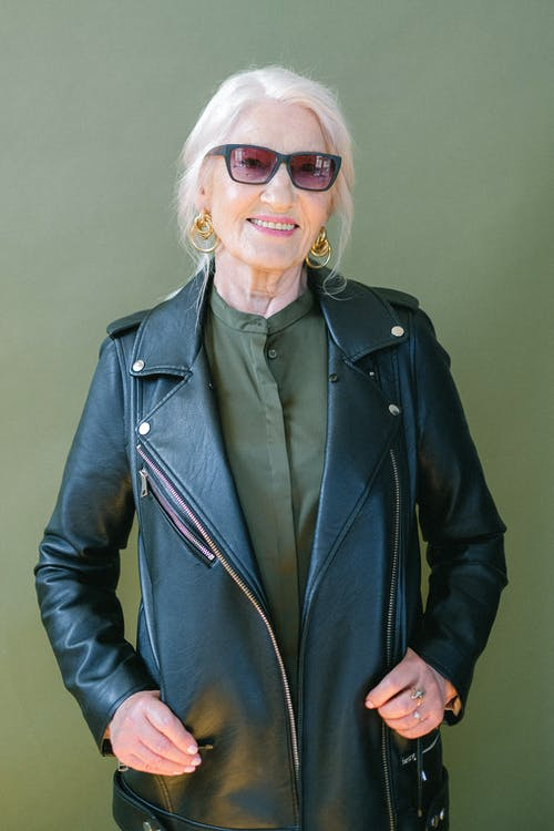 Trendy senior happy woman in sunglasses and stylish leather jacket