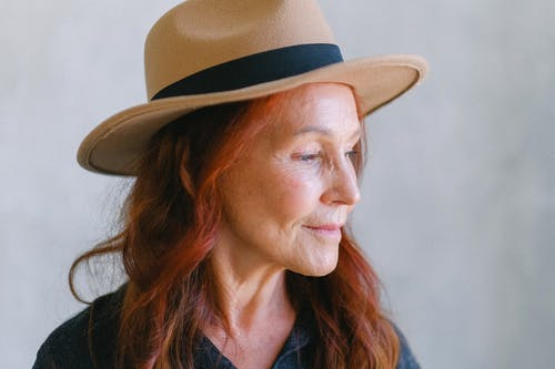 Senior woman with wrinkles and red hair in hat