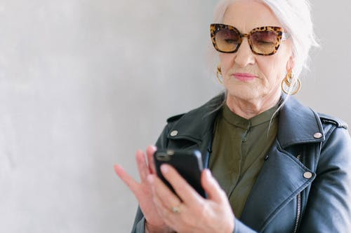 Aged woman in trendy sunglasses touching screen of smartphone