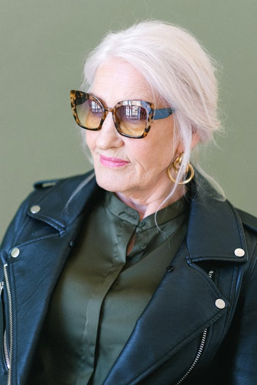 Aged woman in fashionable sunglasses in studio