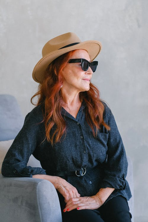 Woman in Black Button Up Long Sleeve Shirt Wearing Brown Hat