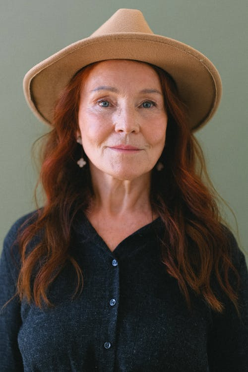 Aged woman with red hair in trendy hat