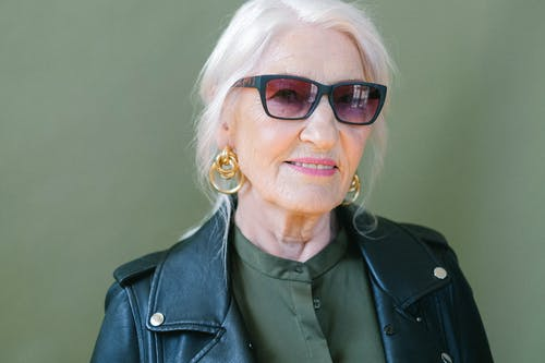Crop aged confident female in stylish leather jacket and sunglasses looking at camera on green background of studio