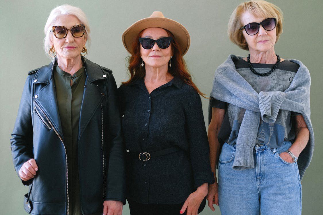 Aged fashionable women in sunglasses and stylish outfit looking at camera on green background