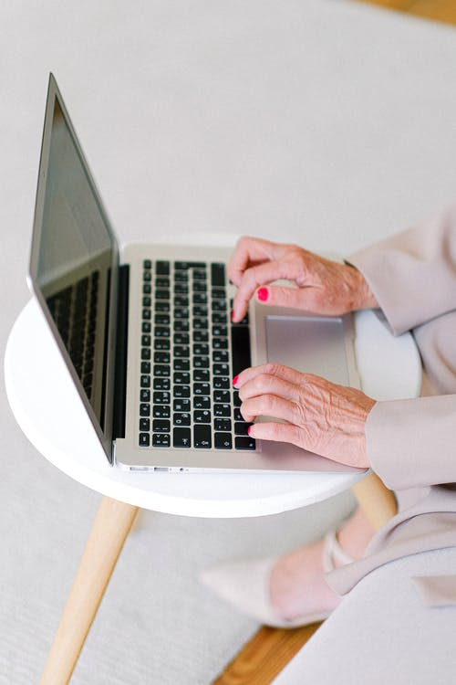 From above of crop anonymous elderly female typing on keyboard of netbook while surfing internet