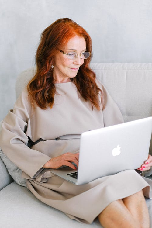 Aged businesswoman in eyeglasses typing important report on laptop