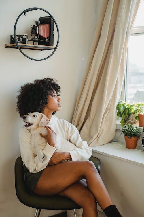 Người Phụ Nữ Da đen Thư Giãn Trên Ghế Với Con Chó