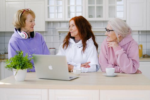 Positive senior women standing at table in kitchen and communicating