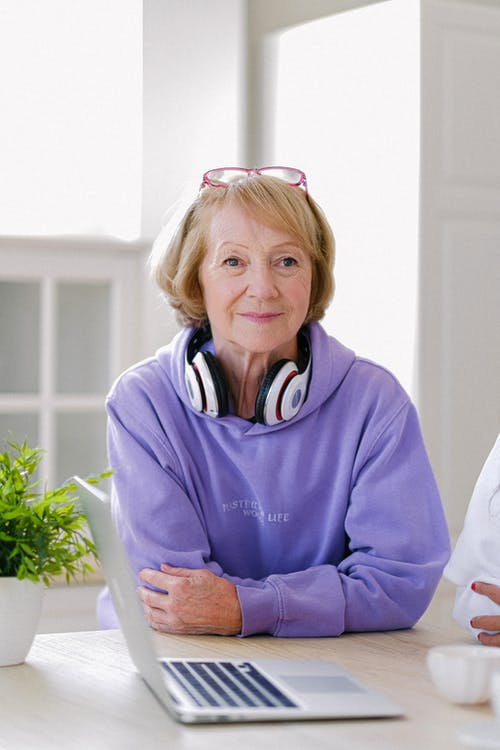 Cheerful senior woman with headphones in stylish outfit sitting at table with netbook in light apartment in daytime