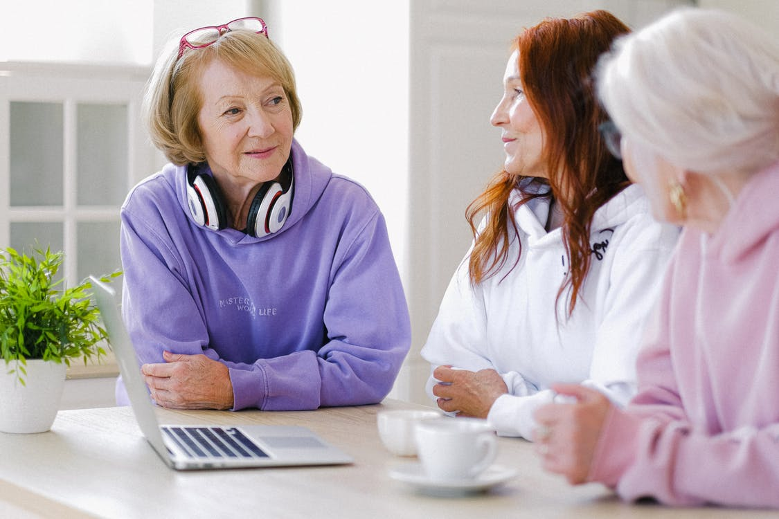 Cheerful aged women in trendy clothes sitting at table with cups of tea and laptop and communicating at home in daytime