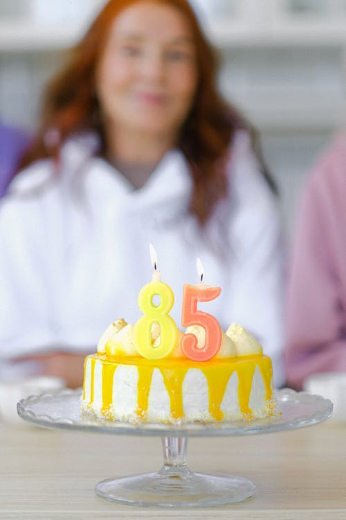 Appetizing birthday cake with burning candles placed on glass plate on table against blurred senior woman