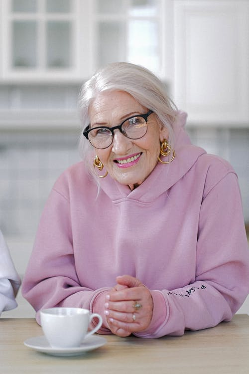Smiling aged woman in hoodie sitting at table in light apartment