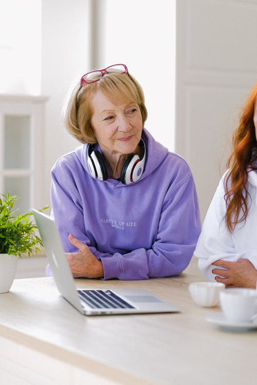 Cheerful senior woman with headphones in stylish hoodie sitting at table with opened netbook and cups of tea while talking with friends in room