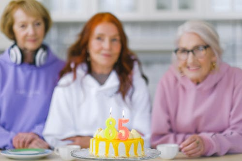 Birthday cake against blurred senior women in light room
