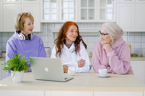 Positive senior women in trendy outfits sitting at table with cups of tea and laptop and communicating in light kitchen at home