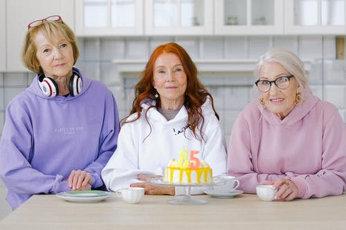 Senior women friends sitting at table with birthday cake