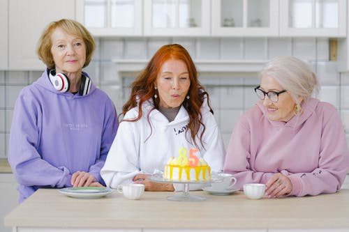 Cheerful aged woman with long red hair in white hoodie blowing out candles on birthday cake during celebration anniversary with friends at home