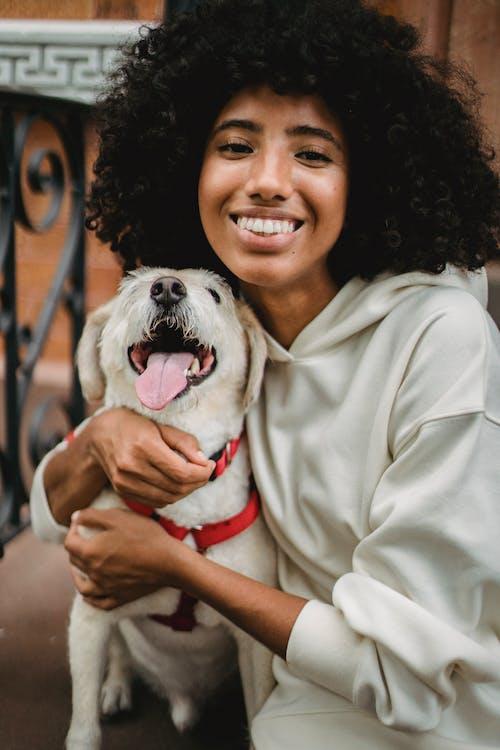 Happy black woman cuddling dog on street