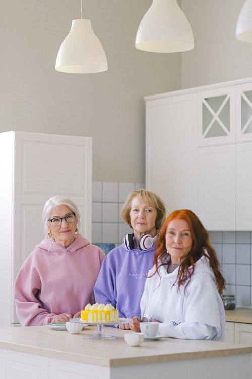 Calm elderly female friends dressed in casual hoodies standing together near table and preparing tea and cake for meal and looking at camera