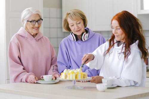 Cheerful woman cutting cake while drinking tea together with female friends