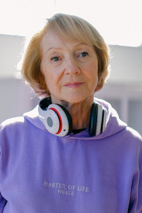 Modern blonde short haired elderly woman in hoodie with headphones looking at camera thoughtfully