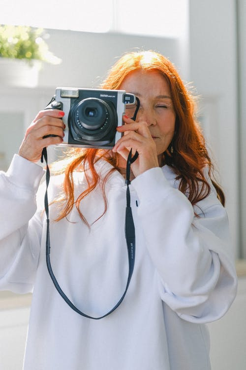 Senior red haired woman with vintage camera