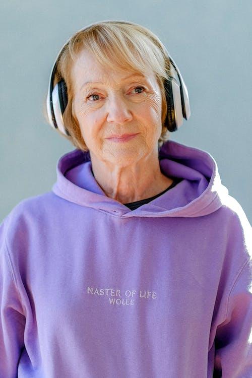 Senior female in trendy hoodie and headphones on blue background listening to music